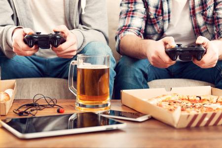 jugando videojuegos: Jugando videojuegos. Primer plano de dos hombres jugando juegos de video mientras se est� sentado en el sof�