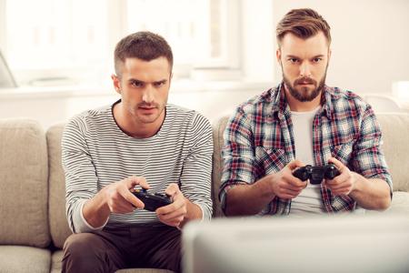 jugando videojuegos: Centrado en juego. Dos jóvenes concentrados jugando juegos de video mientras se está sentado en el sofá
