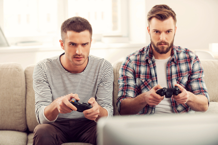 Focused on game. Two concentrated young men playing video games while sitting on sofa Фото со стока