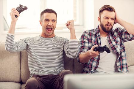 jeu: Amis et jeux vid�o. Deux beaux jeunes hommes jouant � des jeux vid�o alors qu'il �tait assis sur le canap� Banque d'images