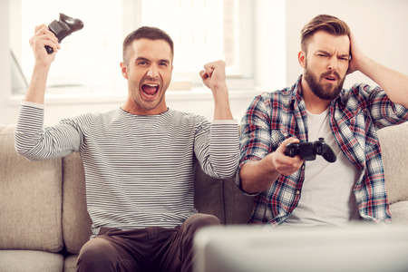 negativity: Friends and video games. Two handsome young men playing video games while sitting on sofa Stock Photo