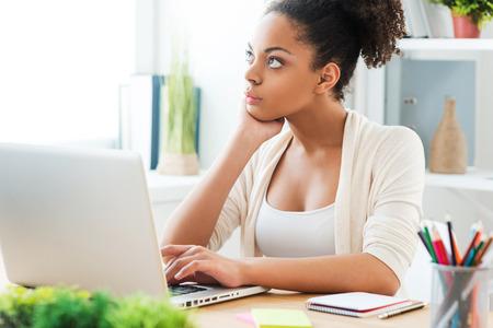 pensamiento creativo: Pensando en soluci�n. Mujer africana joven hermosa que trabaja en la computadora port�til y mirando a otro lado mientras estaba sentado en su lugar de trabajo en la oficina