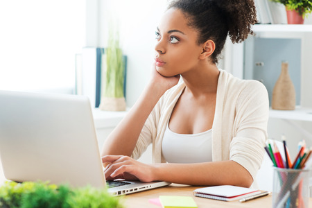woman think: Thinking about solution. Beautiful young African woman working at the laptop and looking away while sitting at her working place in office