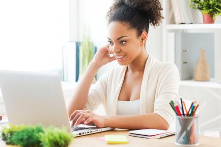 Werken bij nieuwe creatieve project. Mooie jonge Afrikaanse vrouw werken op de laptop en glimlachen tijdens de vergadering op haar werkplek in het kantoor