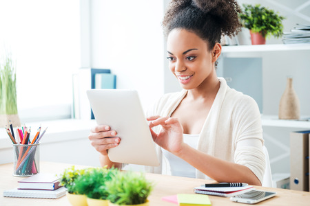 one young adult woman only: Working on tablet. Beautiful young African woman working on digital tablet and smiling while sitting at her working place in office