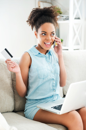 Enjoying online shopping. Attractive young African woman talking on the mobile phone and holding credit card while sitting on the couch with laptop at her knees photo
