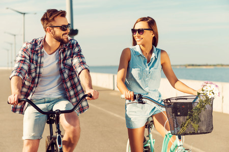 summer beauty: How about race? Cheerful young couple looking at each other with smiles while riding on bicycles along the road Stock Photo
