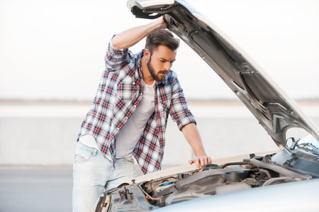 Car breakdown. Concentrated young man holding hands on vehicle hood and looking inside it while standing outdoors