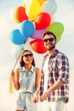 heterosexual couple: Bright love. Cheerful young couple holding hands and smiling while walking outdoors with colorful balloons Stock Photo