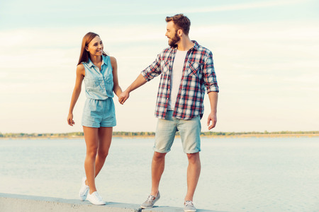 holding hands while walking: Walking through life hand in hand. Loving young couple holding hands and smiling while walking outdoors Stock Photo