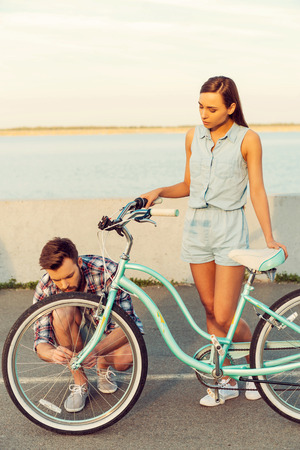 rely: I can rely on him in any situation. Frustrated young women standing behind her bicycle while man repairing a wheel