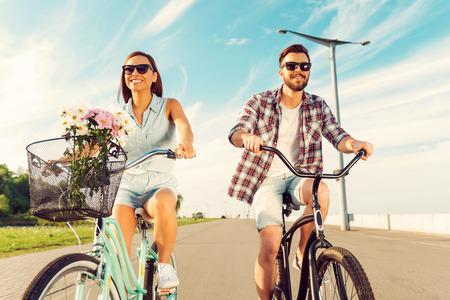 ciclismo: Un gran d�a para el ciclismo. �ngulo de visi�n baja de pareja alegre joven sonriente y montar en bicicletas