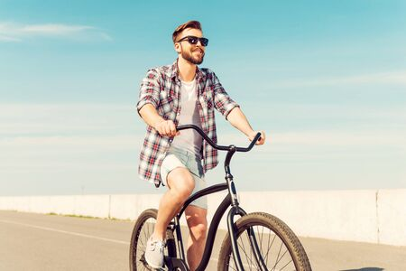 best way: Best way to start a day. Happy young man in eyewear riding bicycle and smiling