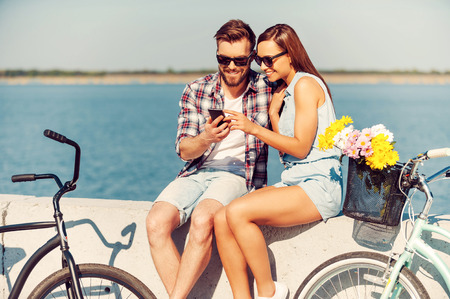 Look at this picture! Smiling young couple looking at mobile phone while sitting outdoors near their bicycles