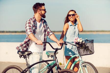 casal: Eles amam a vida ativa. Jovem casal feliz rolando suas bicicletas e olhando para o outro com smileswhile caminhar ao ar livre