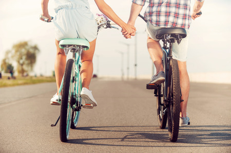bicycles: The perfect summer date. Rear view of young couple holding hands while riding on bicycles along the road Stock Photo