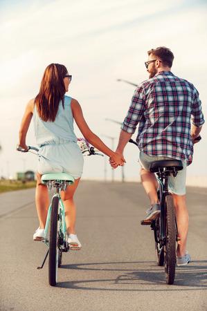 완벽한 날짜입니다. 길을 따라 자전거를 타고있는 동안 젊은 부부가 손을 잡고의 후면보기 스톡 콘텐츠