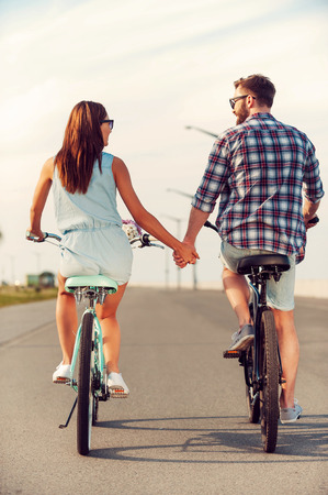 Perfect date. Rear view of young couple holding hands while riding on bicycles along the road Banco de Imagens