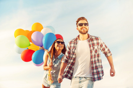 holding hands while walking: Living life to the fullest. Cheerful young couple holding hands and smiling while walking outdoors with colorful balloons