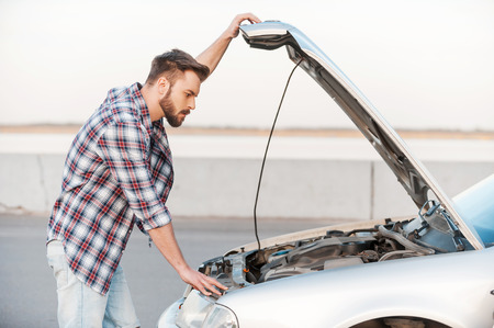 car trouble: Car trouble. Serious young man holding hands on vehicle hood and looking inside it while standing outdoors Stock Photo
