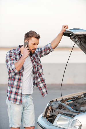 engine bonnet: I need help! Frustrated young man talking on the mobile phone and holding hand on vehicle hood while standing outdoors Stock Photo