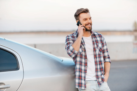 one young man: Inviting friend for a journey. Handsome young man talking on the mobile phone and smiling while leaning at his car