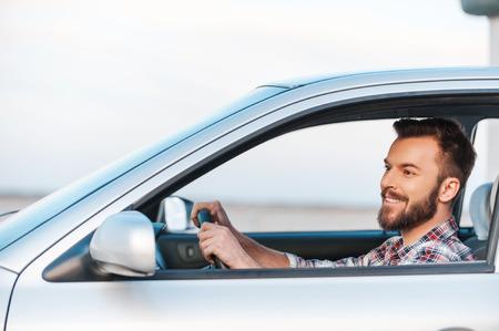 hombre manejando: Montado en su nuevo coche. Vista lateral del hombre joven hermoso al volante de su coche y sonriente Foto de archivo