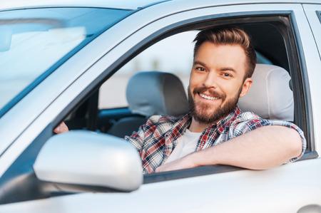 Ik hou van mijn auto! Knappe jonge man rijden zijn auto en glimlachen op camera