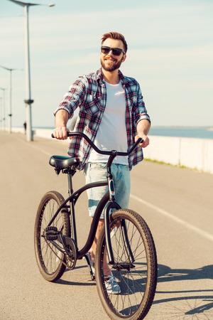 ciclismo: Tiempo para un ciclo. Hombre sonriente joven hermoso que recorre a lo largo de un camino con su bicicleta