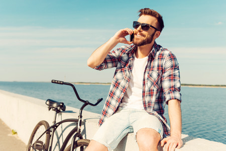 Perfect day for cycling! Cheerful young man talking on the mobile phone and smiling while sitting on parapet near his bicycle