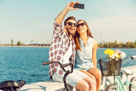 bicicleta: El cobro de los momentos brillantes. Sonriente joven pareja toma selfie mientras está sentado en el parapeto cerca de sus bicicletas