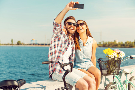 lifestyle: Het verzamelen van de heldere momenten. Glimlachend jong paar dat selfie zittend op borstwering in de buurt van hun fietsen