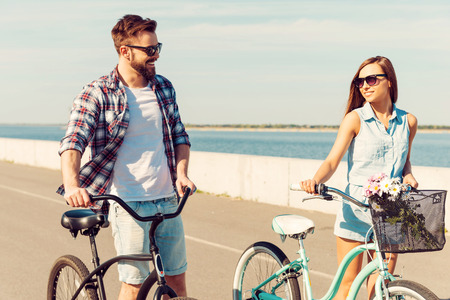 outdoor pursuit: Keeping fit and having fun. Happy young couple rolling their bicycles and looking at each other with smile while walking outdoors