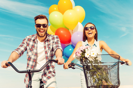 This is so much fun! Low angle view of cheerful young couple smiling and riding on bicycles with colorful balloons in the background