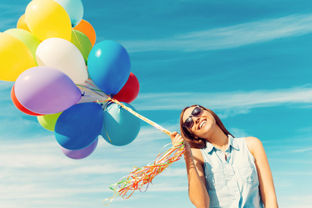 childlike: Feeling childlike. Happy young woman holding colorful balloons and smiling while standing against the blue sky