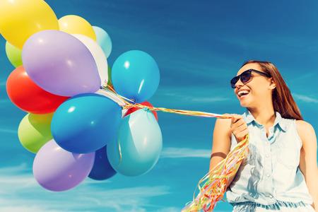 cheerful woman: Escapar de la realidad. �ngulo de visi�n baja de una mujer joven alegre que sostiene los globos coloridos y sonriendo mientras est� de pie contra el cielo azul Foto de archivo