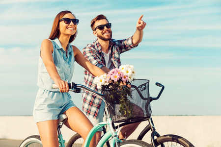 beautiful scenery: What a beautiful scenery! Smiling young couple riding on bicycle while man pointing away
