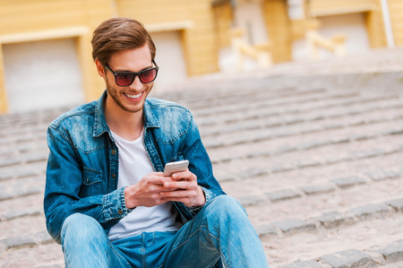 young man: Good spending time in his city. Confident young man holding mobile phone while sitting outdoors