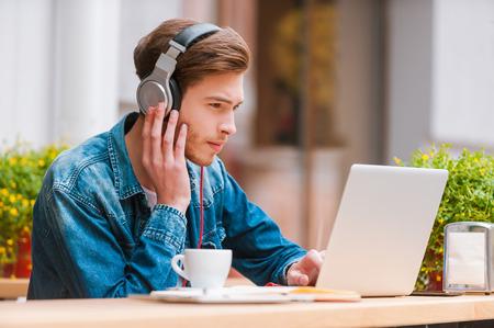 好きな音楽は、私の生産性を向上させます。歩道のカフェに座っている間のラップトップに取り組んでのヘッドフォンでまじめな若者
