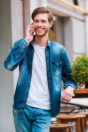 Ya estoy aquí! Alegre joven hablando por teléfono móvil y sonriendo a la cámara mientras está de pie en el café de la acera