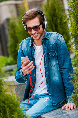only young men: Being on my own wave. Happy young man in headphones holding mobile phone and smiling while sitting outdoors
