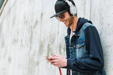 audifonos: Disfrutar de su música favorita. Hombre joven sonriente en los auriculares que sostiene el teléfono móvil mientras se apoya en la pared de hormigón Foto de archivo
