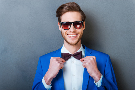 Special detail of his style.Smiling young man in eyewear adjusting bow tie and looking at camera while standing against grey background