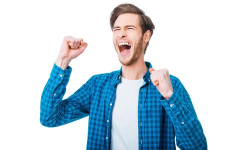 boca cerrada: La victoria está en mi bolsillo. Hombre joven emocionado que mantener los brazos en alto y expresando positividad mientras está de pie contra el fondo blanco Foto de archivo