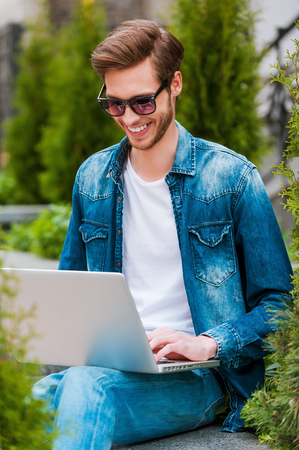 surfing the web: Surfing web outdoors. Smiling young man working on laptop while sitting outdoors