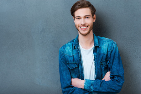male beauty: Confident and handsome. Happy young man keeping arms crossed and smiling at camera while standing against grey background Stock Photo