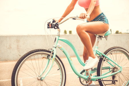 nude female buttocks: Beauty on bicycle. Close-up of beautiful young woman with perfect curves riding bicycle