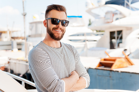 yachtsman: Confident yachtsman. Smiling young man keeping arms crossed and looking at camera while standing on the board of yacht Stock Photo