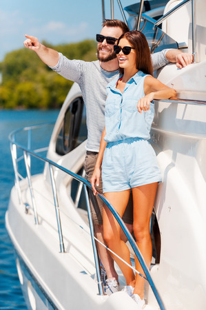 heterosexual couple: This view is amazing! Cheerful young couple looking away and smiling while standing on the board of yacht