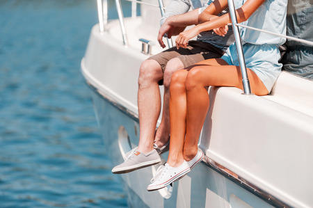 wealth concept: Spending great summer day together. Close-up of young couple sitting on the board of yacht